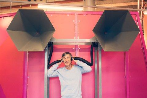 Ein Mann vor pinker Wand mit zwei Rohren an den Ohren