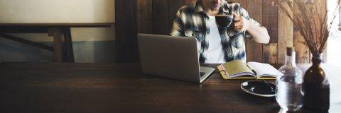 Bild von einem Mann mit Laptop in einem Café