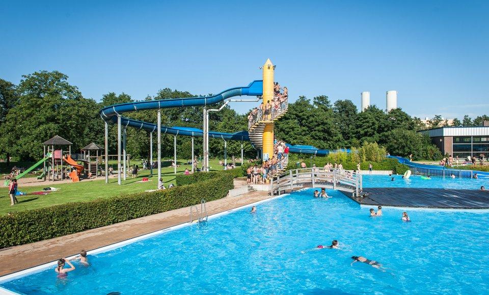 Das Schlossparkbad im Sommer mit großem Außenbecken und einer großen Wasserrutsche.