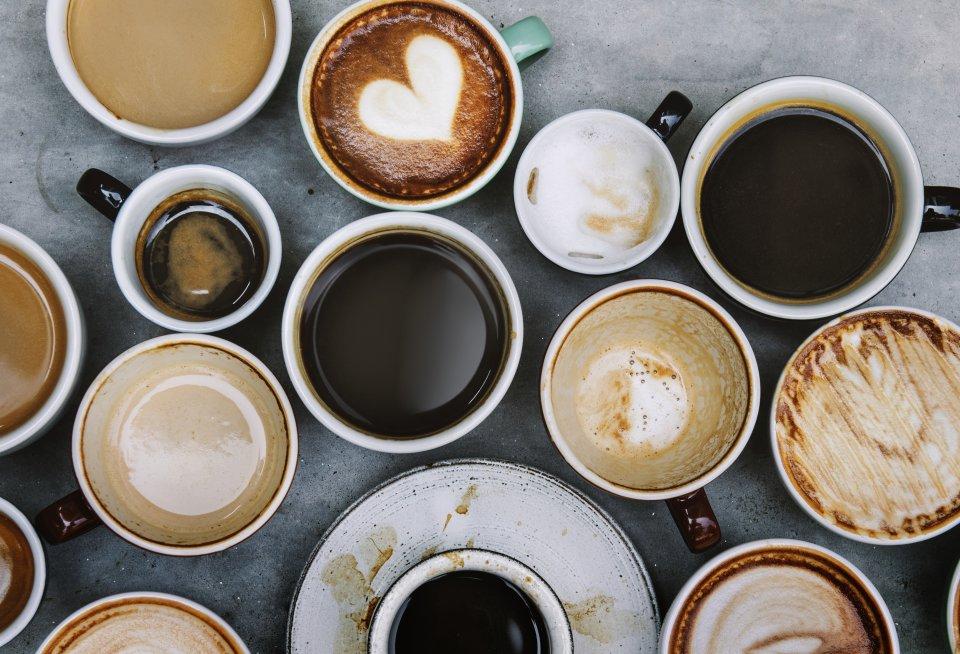 Zahlreiche Becher und Tassen mit unterschiedlichen Kaffeespezialitäten aus der Vogelperspektive