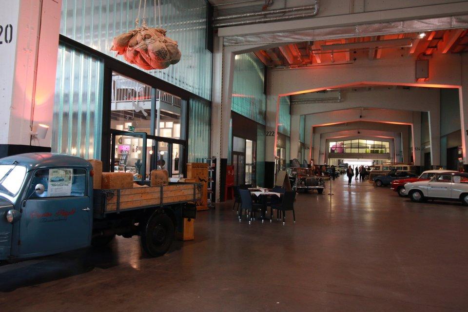 Eine hohe Halle durch die ein breiter Gang führt, dieser ist von älteren Autos umgeben. Links steht ein kleiner blauer Oldtimer-Lastwagen